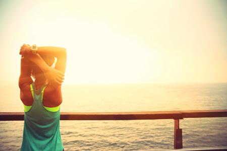 deportes de fitness corredor de la mujer que estira en la playa pasarela de madera