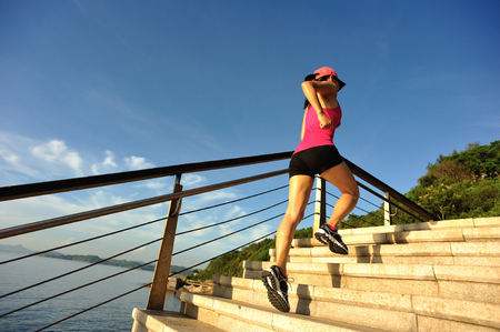 asian natural: young fitness woman runner running on seaside stone stairs