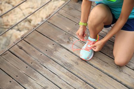 shoelace: sports woman runner tying shoelace on wooden boardwalk seaside