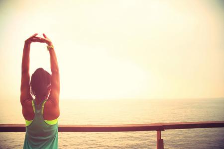 estiramiento: deportes de fitness corredor de la mujer que estira en la playa pasarela de madera