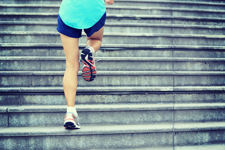 legs: sports woman legs running up on stone stairs Stock Photo