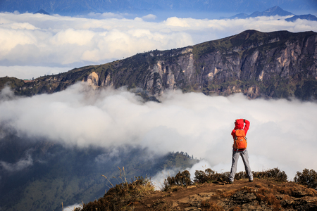 taking photo: young woman photographer taking photo for beautiful landscape on mountain peak Stock Photo