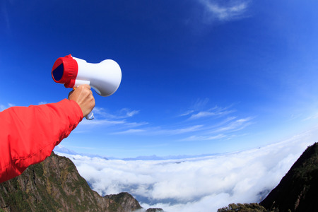 annoucement: people hand hold loudspeaker to blue sky on mountain peak