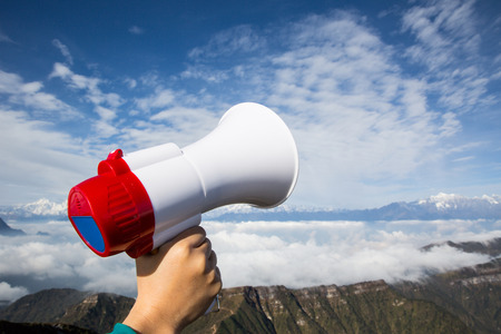 aerophone: hand hold loudspeaker to blue sky on mountain peak Stock Photo