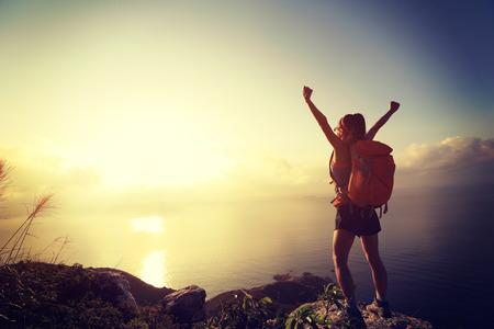 mochila de viaje: animando mujer joven mochilero al amanecer pico de la montaña junto al mar