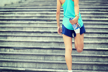 young woman legs up: fitness woman runner stretching legs on stairs