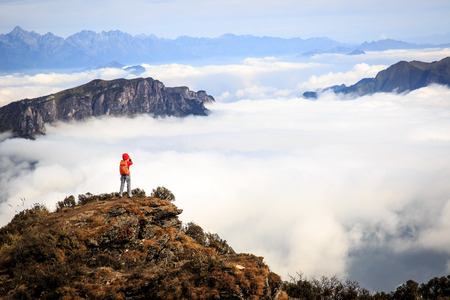 female photographer: young woman photographer taking photo for beautiful landscape on mountain peak Stock Photo