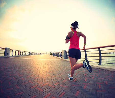 Runner atleta que corre en la playa. Aptitud de la mujer silueta de la salida del sol para correr entrenamiento concepto de bienestar. Foto de archivo