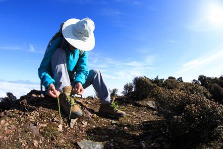 jokul: young woman hiker tying shoelace on beautiful mountain peak