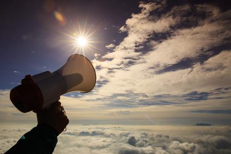 annoucement: hand hold loudspeaker to sky on mountain peak Stock Photo