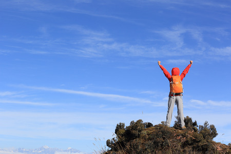 hiking: cheering young woman hiker open arms on mountain peak Stock Photo