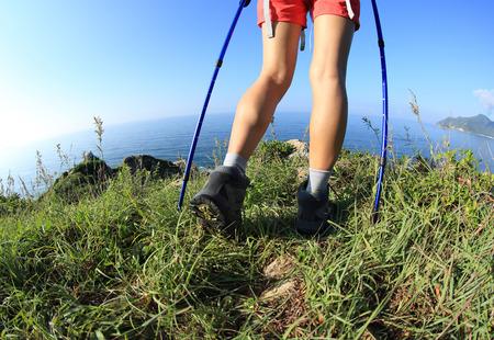 hiking trail: woman hiker legs hiking on seaside mountain grass
