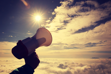 annoucement: hand hold loudspeaker to sky on mountain peak,vintage effect