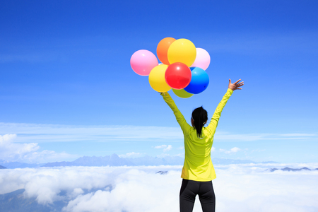 colorful sky: cheering young woman on mountain peak with colorful balloons Stock Photo