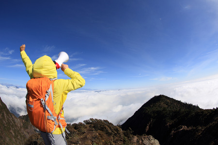 aerophone: young woman backpacker shouting with loudspeaker on beautiful mountain peak