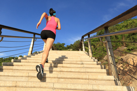 seaside: young fitness woman runner running on seaside stone stairs