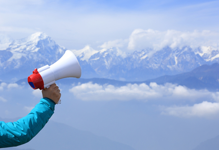 annoucement: hand hold loudspeaker to blue sky on mountain peak Stock Photo