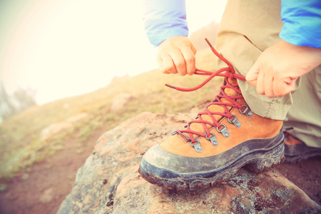 hiking boots: woman hiker tying shoelace on mountain peak