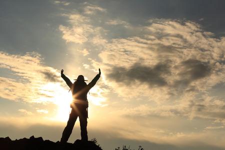 jokul: silhouette of cheering hiker open arms on sunset mountain peak