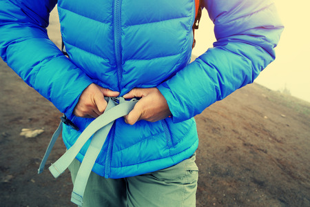 buckle: woman hiker buckle up the belt of backpack on mountain peak Stock Photo