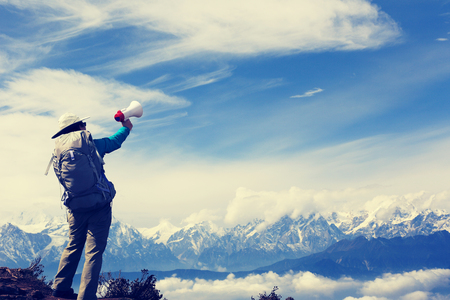 annoucement: young woman backpacker shouting with loudspeaker on beautiful mountain peak,vintage effect