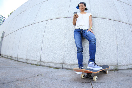 chinese wall: young skateboard use cellphone rest leaning on wall Stock Photo