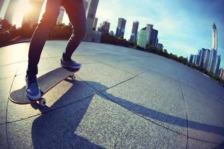 city of sunrise: skateboarder skateboarding at sunrise city Stock Photo