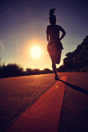 human energy: young fitness woman running on sunrise seaside trail,vintage effect