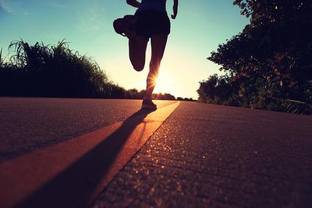 personas corriendo: aptitud de la mujer joven que se ejecutan en la salida del sol sendero junto al mar, efecto vintage Foto de archivo