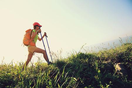 hiking stick: young woman hiking on seaside mountain trail