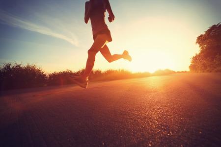 deportista: aptitud de la mujer joven que se ejecutan en el sendero junto al mar la salida del sol