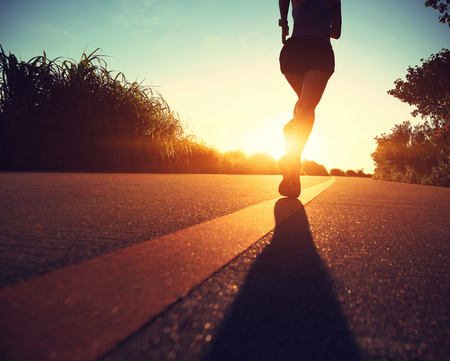 lifestyle outdoors: young fitness woman running on sunrise seaside trail