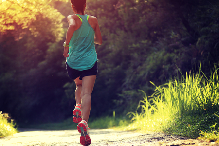 girl jogging: Runner athlete running on forest trail. woman fitness jogging workout wellness concept.