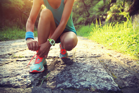shoelaces: young woman runner tying shoelaces on stone trail Stock Photo