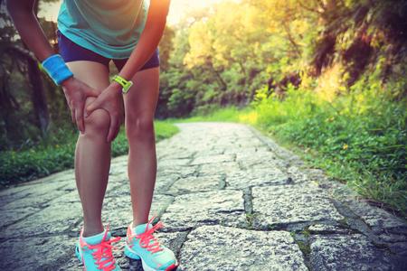 woman runner hold her sports injured knee Foto de archivo