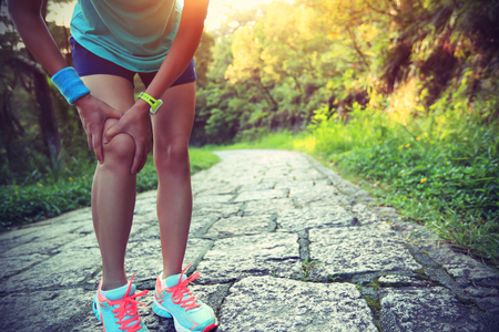 lesionado: woman runner hold her sports injured knee Foto de archivo