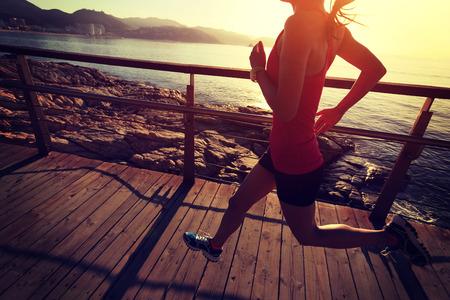 personas corriendo: j�venes piernas de la mujer de la aptitud que se ejecutan en pasarela de madera junto al mar