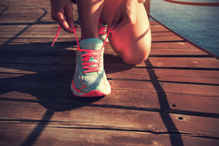 woman freedom: young fitness woman tying shoelace on seaside wooden boardwalk