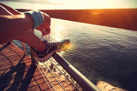 shoelace: young fitness woman tying shoelace on seaside wooden boardwalk