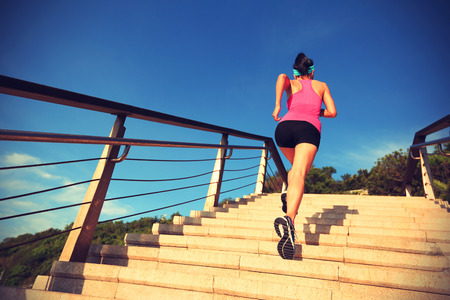 stairs: healthy lifestyle sports woman running up on stone stairs seaside