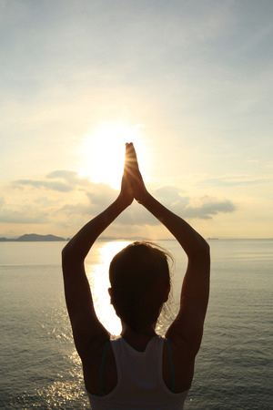 wellness: healthy yoga woman meditation at sunrise seaside Stock Photo