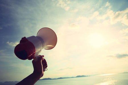 hand hold megaphone with sea under sky background