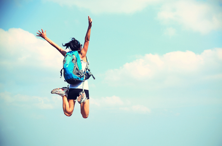 black blue: young asian woman jumping against blue sky Stock Photo