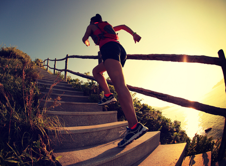 woman stairs: fitness woman runner trail running on seaside mountain stairs, training for cross country running.