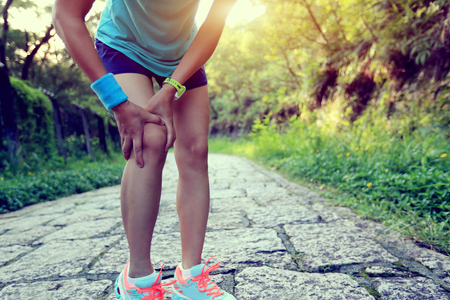 woman runner hold her sports injured knee Imagens
