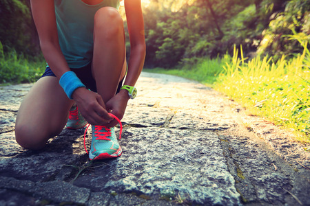 cross ties: young woman runner tying shoelaces on stone trail Stock Photo