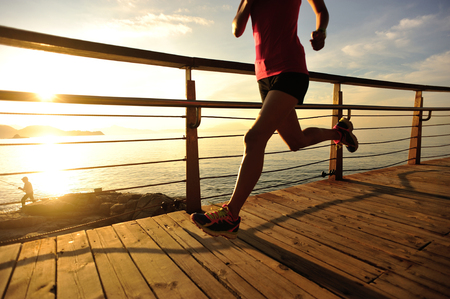 morning sunrise: young fitness woman legs running on sunrise seaside trail Stock Photo