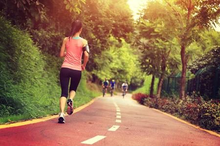 personas corriendo: aptitud de la mujer joven que se ejecutan en la pista forestal