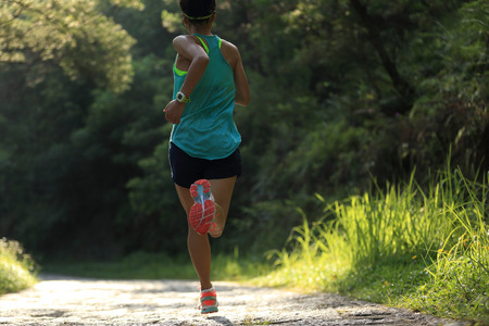green and black: Runner athlete running on forest trail. woman fitness jogging workout wellness concept.