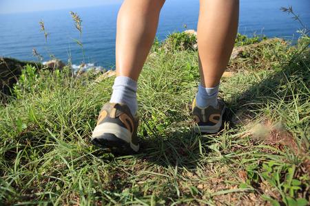 hiking: woman hiker legs hiking on seaside mountain grass